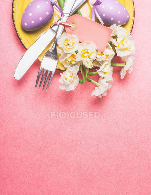 Top view of plate with cutlery on table decorated with easter eggs and spring flowers — Stock Photo