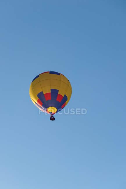 Colorido globo aerostático volando en cielo azul - foto de stock
