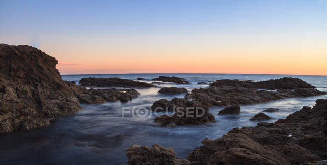 Longue exposition du coucher du soleil sur les rochers — Photo de stock