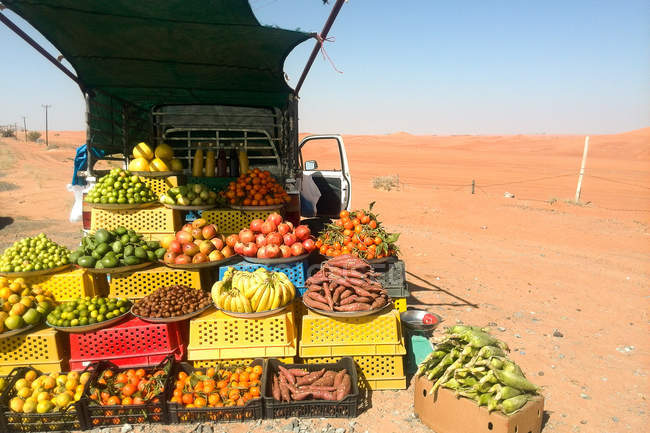 Car with fruits and vegetables in desert, selling food — Stock Photo