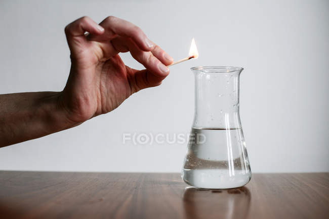 Cropped view of person hand holding match over laboratory flask — Stock Photo