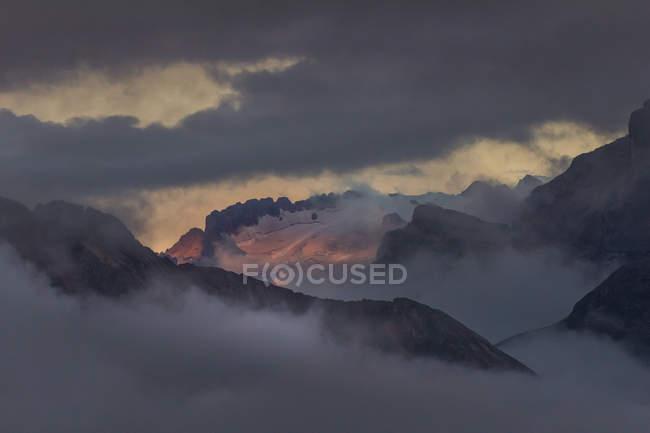 Мальовничі чаруючим підносяться сніг і туман покриті гірські вершини — стокове фото