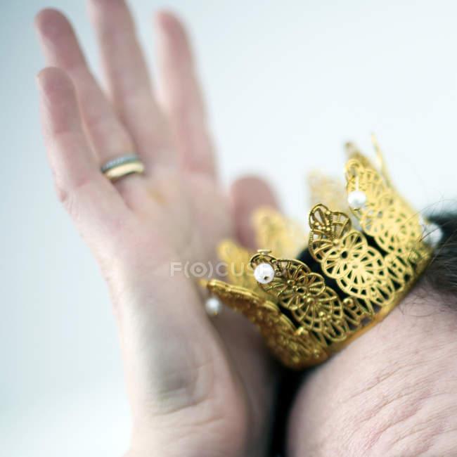Женщина, регулируя Золотая Корона на голове — стоковое фото