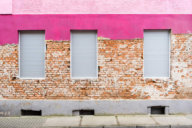Building brick wall surface and pink painted facade — Stock Photo