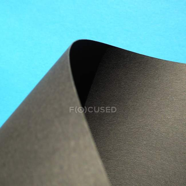 Scrolled black paper on blue background — Stock Photo