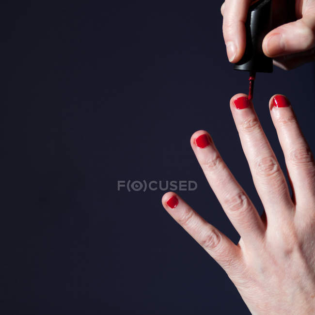 Cropped View Of Female Hands Painting Nails With Red Nail Polish Stock Photo