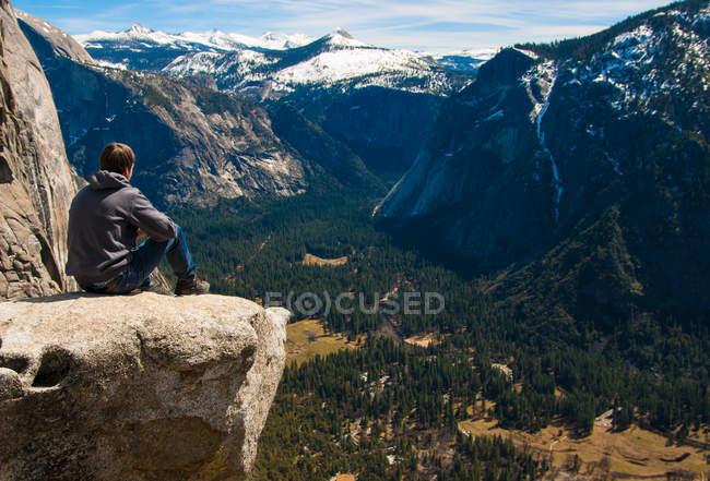 Homem viajante sentado no topo de montanhas — Fotografia de Stock