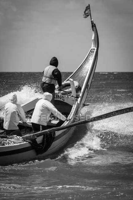 Vue arrière de trois hommes natation en bateau à l'océan, monochrome — Photo de stock