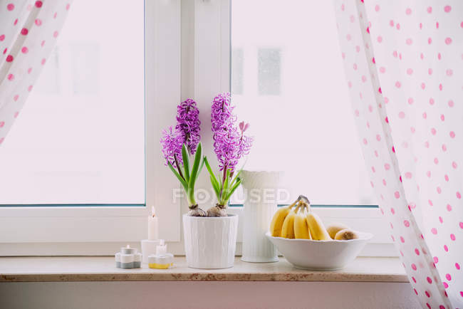 Bananas with candles and plants on window sill — Stock Photo