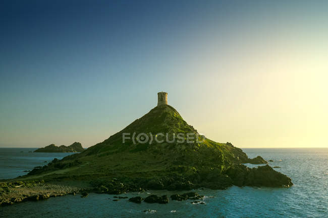 Seascape with tower on the top of green hill, Corsica, France — Stock Photo