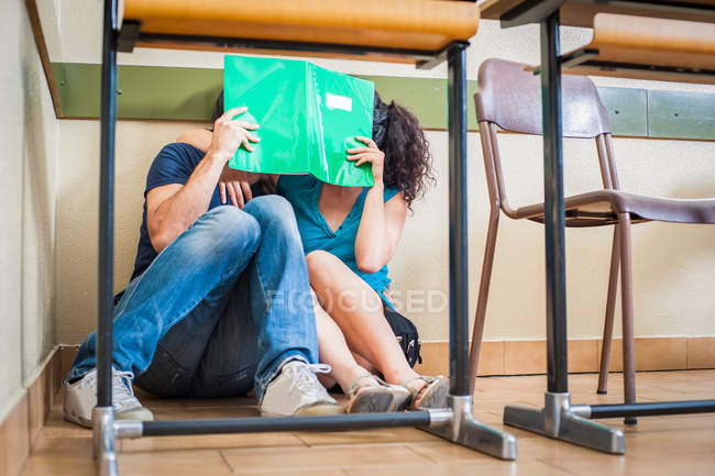 Couple students kissing in classroom — Stock Photo