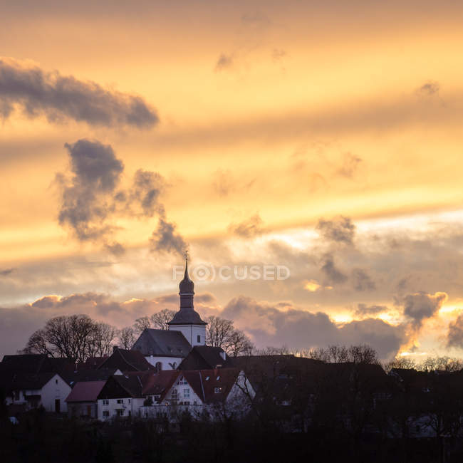 Architecture buildings in small village with houses and church, sunset sky — Stock Photo