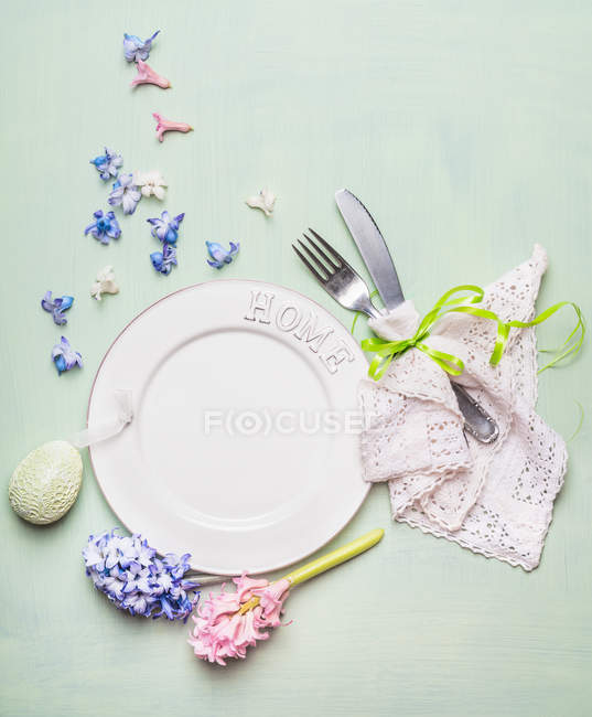 Top view of plate with cutlery on table decorated with easter egg and spring flowers — Stock Photo