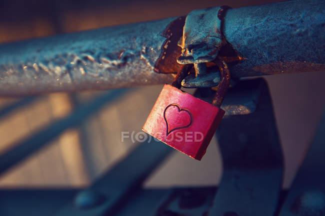 Padlock with heart sign on iron railing — Stock Photo