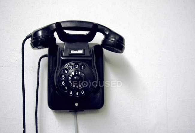 Old fashioned telephone with rotary dial hanging on wall — Stock Photo
