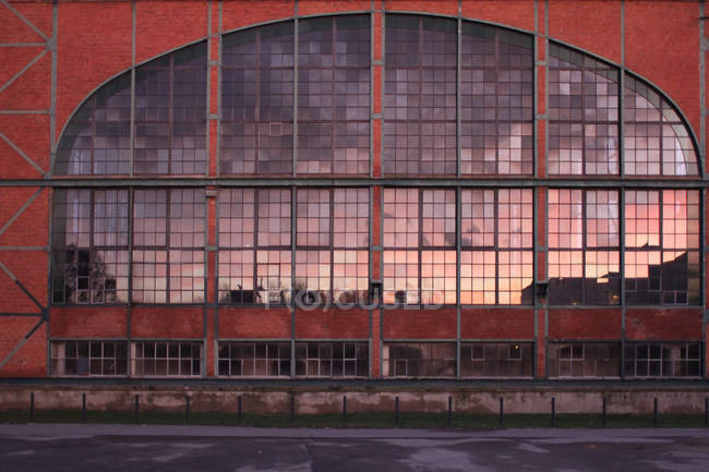 Modern factory building exterior, architecture construction with glass windows and sunset reflection — Stock Photo