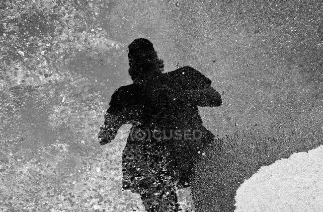 Shadow of man reflected in puddle — Stock Photo