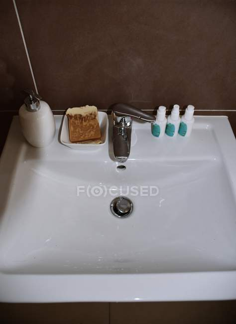 Elevated view of clay sink with soap and bottles with cosmetics — Stock Photo