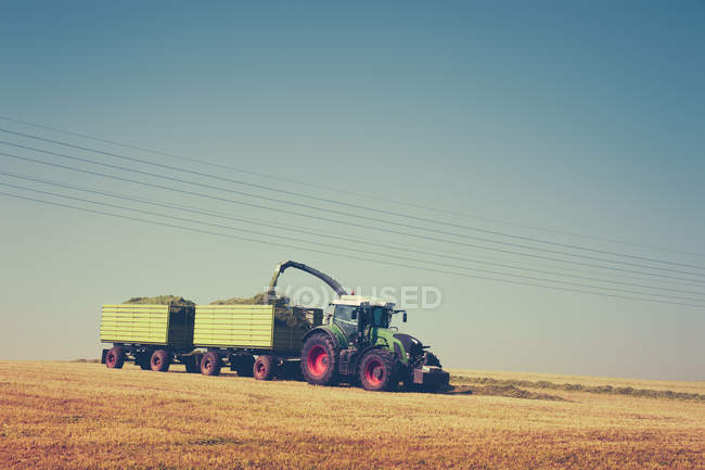 Daytime view of tractor harvesting crop on field — Stock Photo