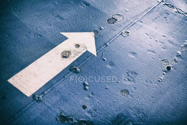 Blue road covering and white straight arrow sign — Stock Photo