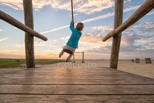 Back view of little boy having fun on rope swing — Stock Photo