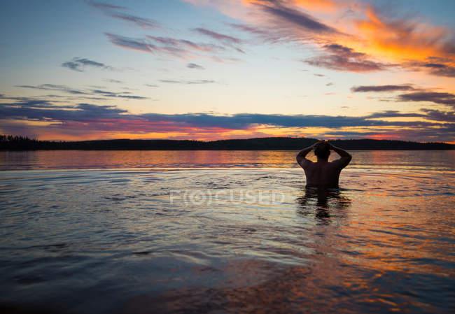 Blick auf die Bucht und männliche Silhouette im Wasser — Stockfoto