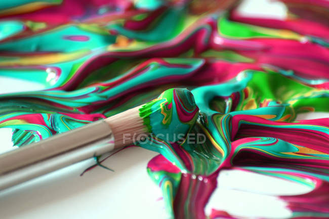 Closeup of brush in colorful acrylic paints — Stock Photo