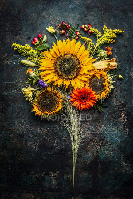 Top view of sunflowers themed design on dark background — Stock Photo