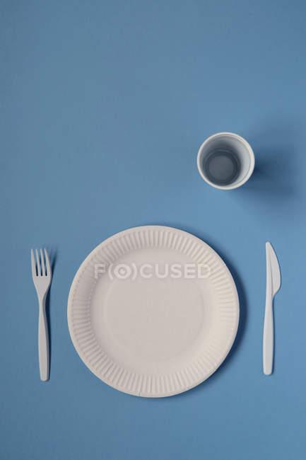 Vista superior del plato con cubiertos de plástico en la mesa - foto de stock