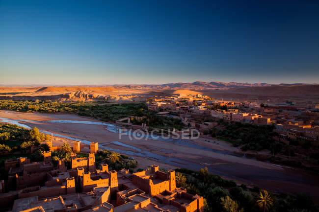 Pôr do sol no deserto com a pequena vila de casas — Fotografia de Stock