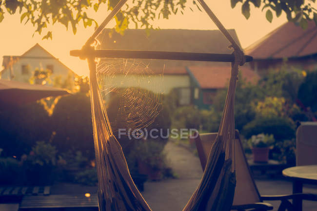 Spider net on hammock near house yard with sunset sunbeams — Stock Photo