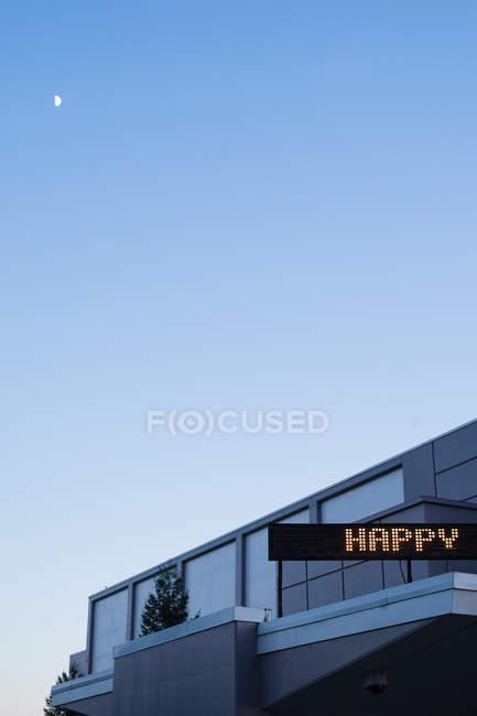 Gebäude-Fassade mit Schriftzug Anzeige, digitale Anzeige mit Text glücklich — Stockfoto