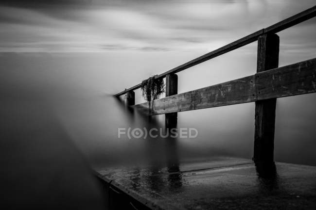 Foggy seascape with broken footdridge — Stock Photo