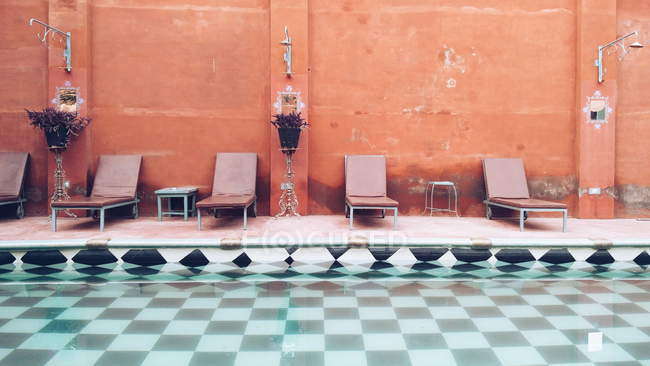 Design of inner swimming pool with tiled flooring and deck chairs around — Stock Photo