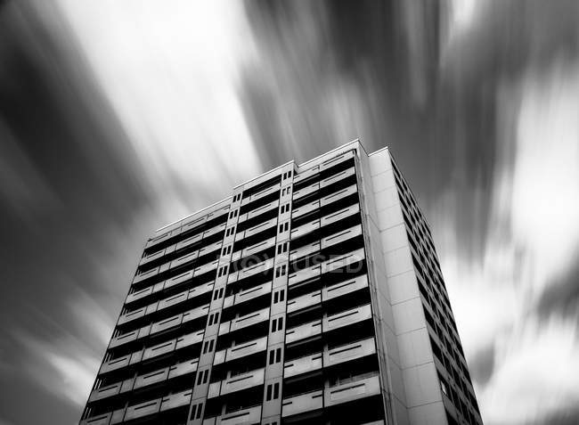 High rise building facades of modern architecture, bottom view, sky in motion blur — Stock Photo