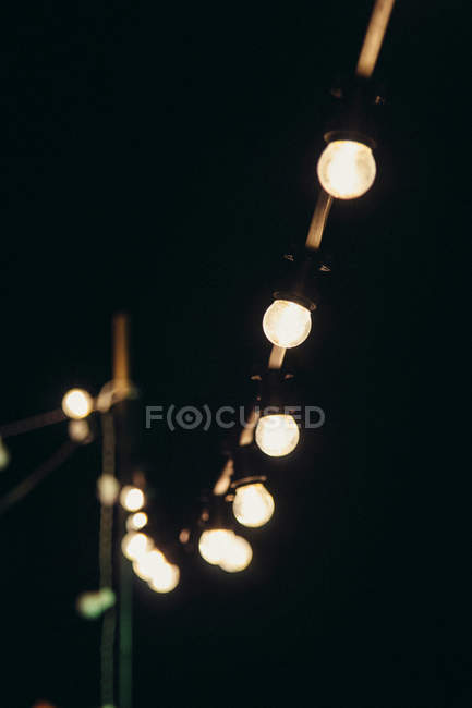 Garland of glowing bulbs, dark background — Stock Photo