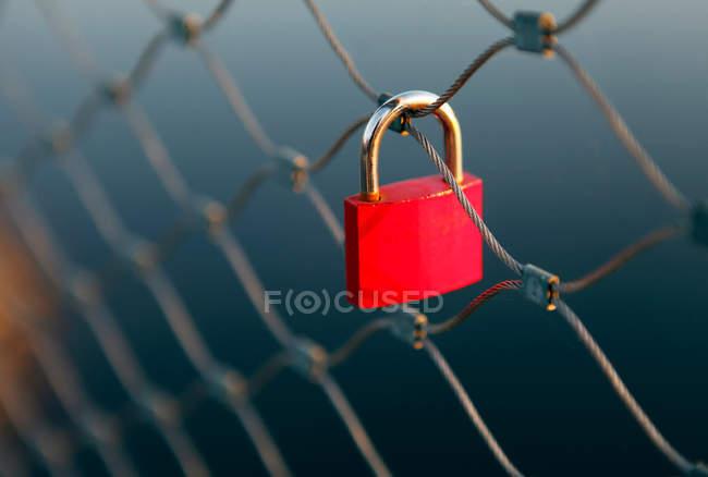 Red padlock hanging on iron gate — Stock Photo