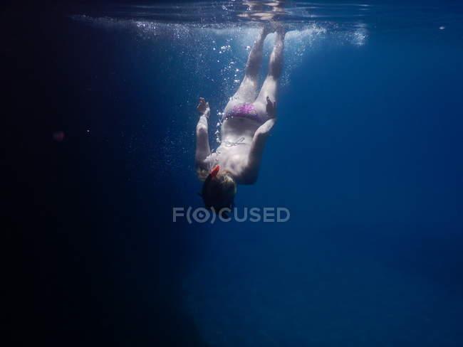 Giovane donna che nuota sott'acqua, posteriore vista — Foto stock