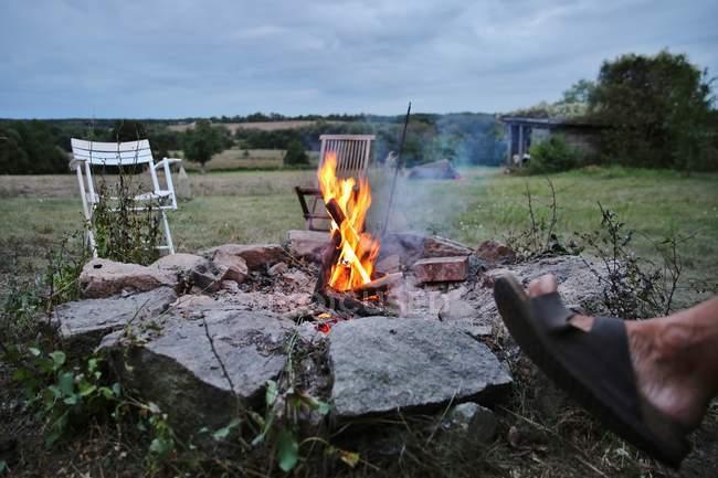 Zugeschnittenes Bild des menschlichen Fußes in der Nähe von Lagerfeuer mit Stühlen — Stockfoto