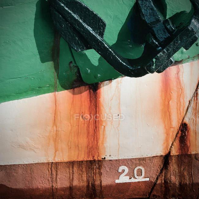 Ржавый корабль окрашенные стены с зеленым якорь и уровень воды маркировки — стоковое фото