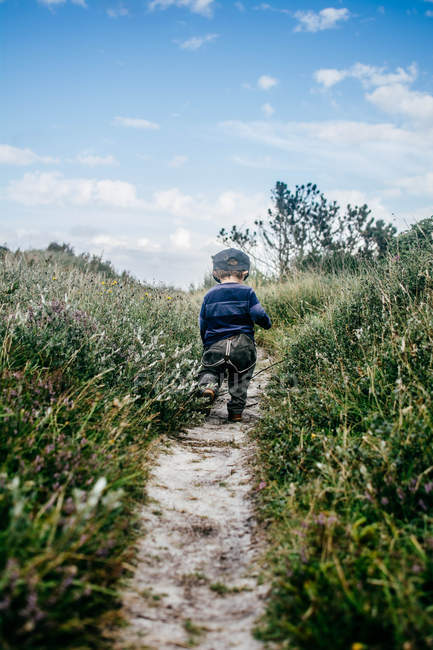 Back view of child walking on path in field — Stock Photo