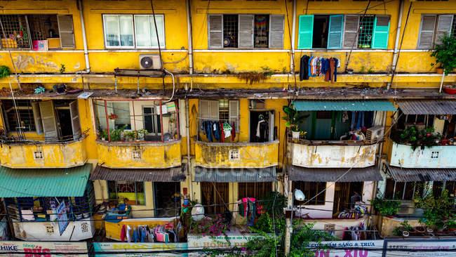 Giallo vecchia casa residenziale con balconi sulla facciata squallido — Foto stock