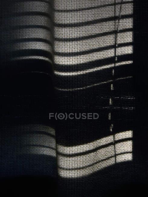 Quarto escuro, janela com cortina e sombras de luz — Fotografia de Stock