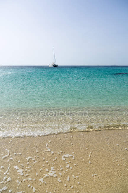 Summer sand beach and crystal clear ocean water with floating boat — Stock Photo