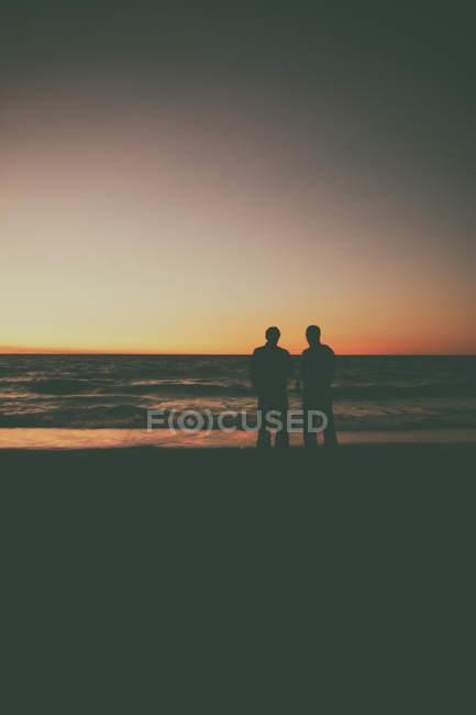 Men standing on the beach — Stock Photo