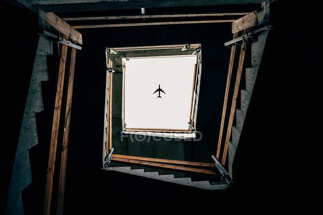 Unteransicht des quadratischen Treppe und fliegenden Flugzeug — Stockfoto