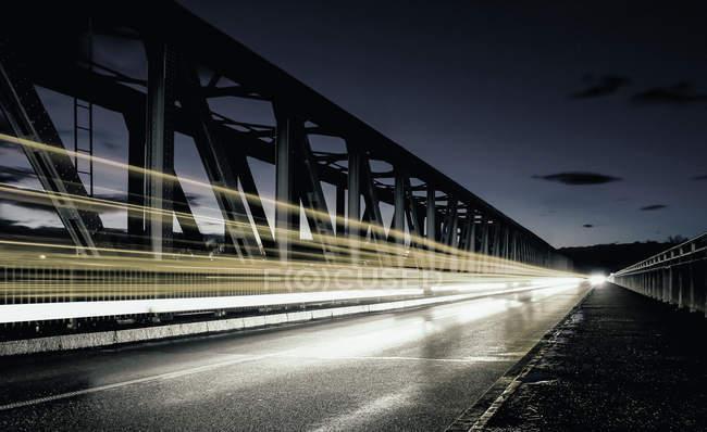 Eisenbahn-Brücke und Verkehr Bewegungsunschärfe bei Nacht Tomé — Stockfoto