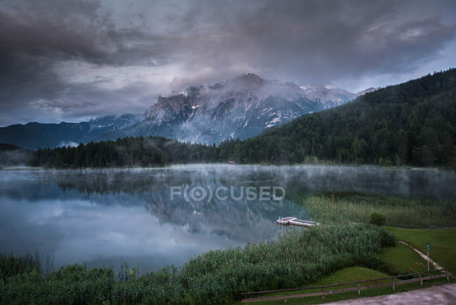 Scenic landscape with mountains and forest by lakeside in moody weather day — Stock Photo
