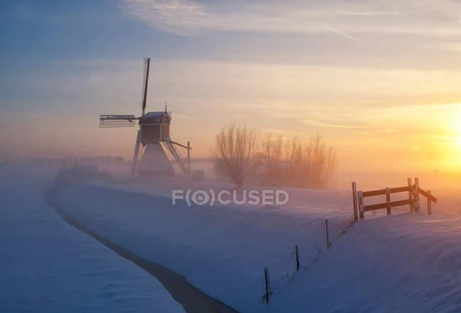 Windmill silhouette on snowy field — Stock Photo