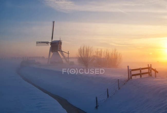 Windmill silhouette on snowy field — Stock Photo